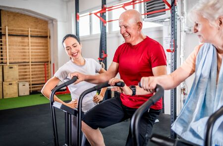 Senior couple biking at the gym with personal trainer