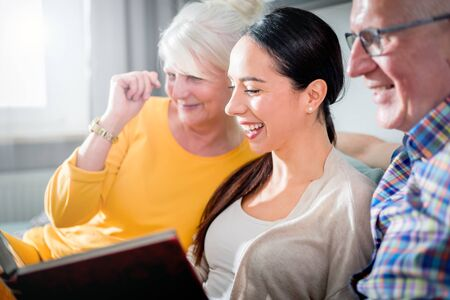 Senior couple with their daughter looking at photos in family album together Reklamní fotografie - 127360218