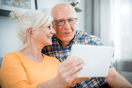 Happy senior couple looking at tablet sitting on sofa at home
