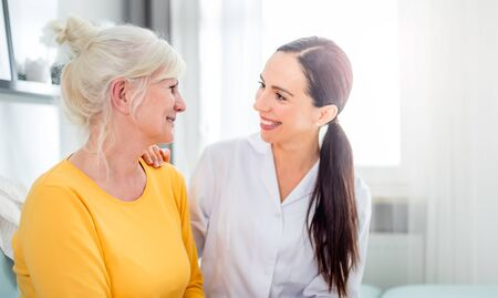 Smiling nurse talking with senior female during home visit 写真素材 - 127360222