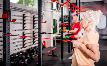 Senior people with trainer using resistance band doing exercises at the gym Reklamní fotografie - 127360226