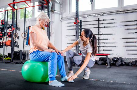 Senior woman with trainer doing rehab using pilates ball in the rehabilitation center 写真素材 - 127360300