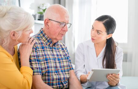 Nurse gives bad news to worried senior couple at home Reklamní fotografie - 127360305