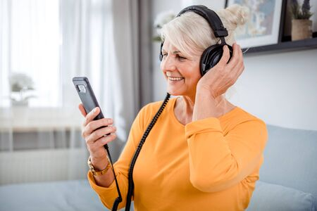 Senior woman listening her favourite music at home using headphones and smartphone 写真素材 - 127360306