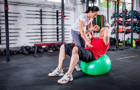 Senior man with trainer doing rehab using pilates ball in the rehabilitation center 写真素材