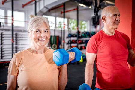 Senior people with dumbbells doing exercises at the gym 写真素材 - 127360317
