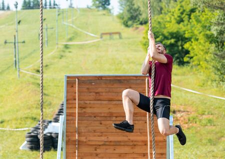Overcome obstacle using rope during extreme race in the boot camp Stockfoto