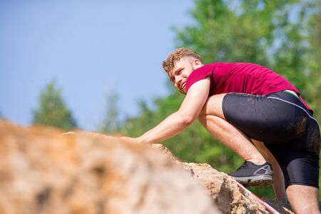 Runner climbing on rocks obstacles in the extreme cross-country race