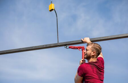 Fit man climbing on obstacles at the extreme race in the boot camp Stockfoto