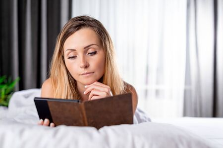 Relaxed pretty woman reading book using ebook reader or tablet lying on bed