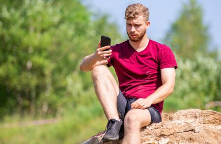 Fit man using smartphone with sport app during training outdoor