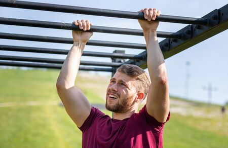 Runner overcome obstacle by hands during extreme race in the boot camp
