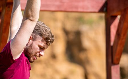 Fit man overcome obstacles using rings during extreme race in the boot camp