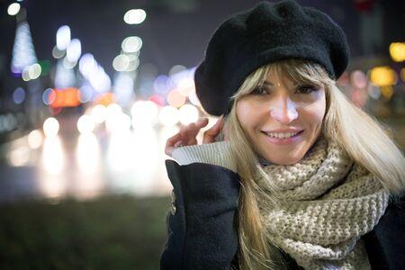 Pretty young stylish woman walking in the night city streets, bokeh illumination background