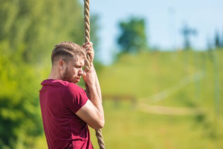 Overcome obstacle using rope during extreme race in the boot camp Reklamní fotografie