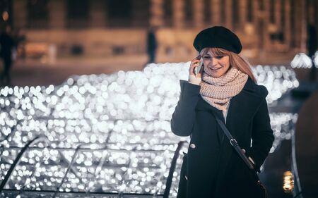 Pretty woman standing at illuminated alley talking phone with Christmas wishes