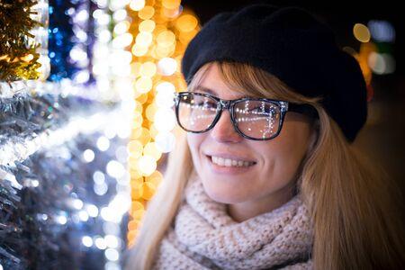 Happy smiling stylish woman walking on illuminated city street during Christmas night