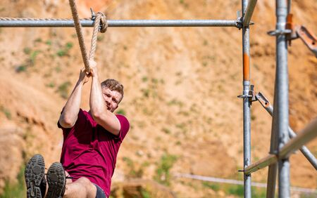 Fit man overcome obstacles using rope during extreme race in the boot camp