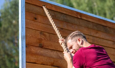 Man overcome barriers by hands during obstacle course in the boot camp Reklamní fotografie
