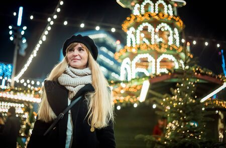Happy smiling girl at Christmas market, illuminated bokeh background