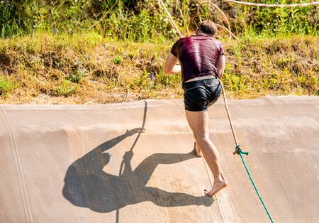 Fit man using rope during obstacle course training in the boot camp 写真素材 - 129519350