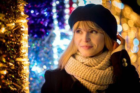 Happy smiling girl walking along illuminated alley during Christmas