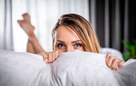 Lovely young woman posing on bed looking at camera with smile Stockfoto