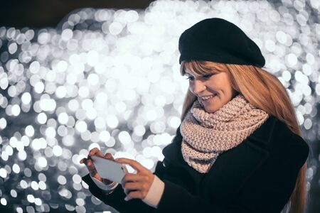 Pretty woman standing at illuminated alley taking photos, outdoor christmas decoration