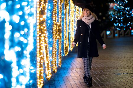 Happy smiling girl among Christmas decorations on city street