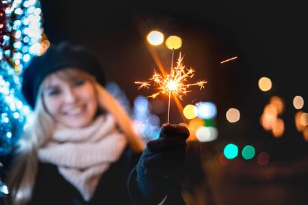 Happy smiling girl holding sparklers standing on illuminated city street during Christmas or New Year night