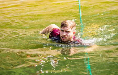 Runner during obstacle course training swims in the pond Reklamní fotografie