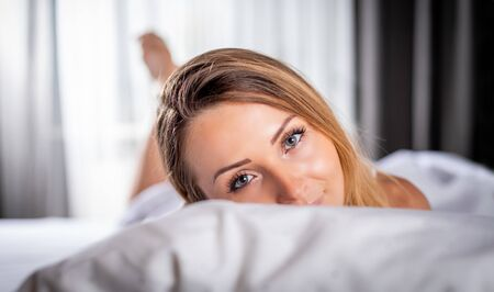 Lovely young woman posing on bed looking at camera with smile Reklamní fotografie