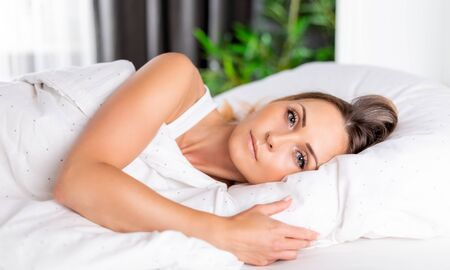 Beautiful woman lying on bed and looking at camera