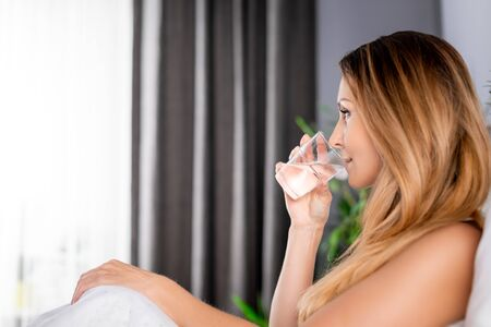 Woman in bed drinking glass of mineral water at morning, healthy lifestyle