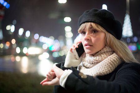Pretty young stylish woman walking in the night city streets using modern smartpone, bokeh illumination background Stockfoto