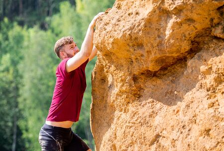 Fit man climbing on rocks obstacles in the boot camp