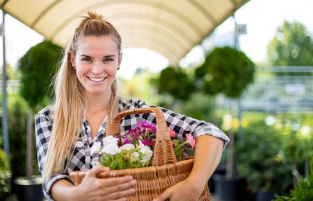 Customer with basket full of flowers in garden center 写真素材