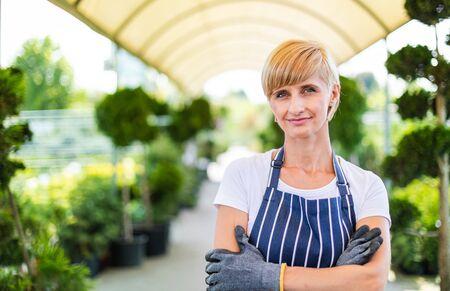 Smiling gardener woman who is employee in garden center