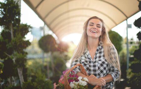 Happy customer in garden center holding basket with flowers 写真素材