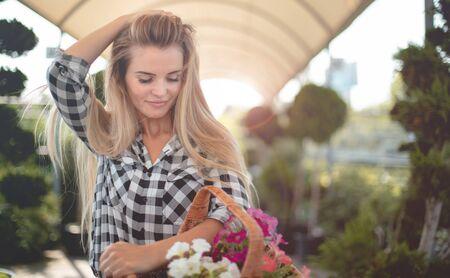 Happy customer in garden center holding basket with flowers Stockfoto