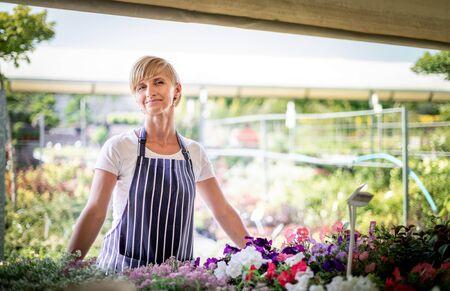 Proud gardener woman who is employee in garden center