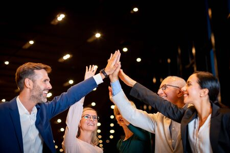 Happy successful diverse business team of all ages giving a high fives gesture as they laugh and cheer their success