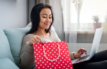 Asian woman holding red gift bag and shopping online using laptop at home