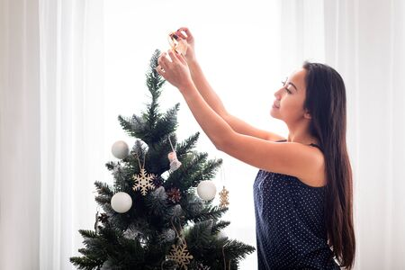 Young Asian woman decorating Christmas tree at home