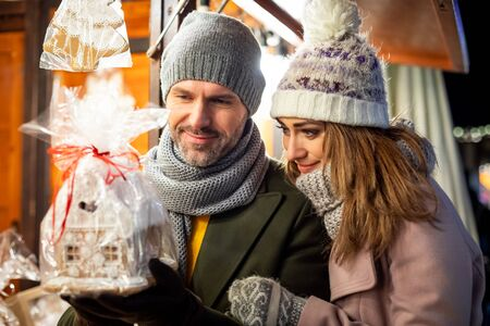 A nice couple spends time together at the Christmas market looking at products in the stalls