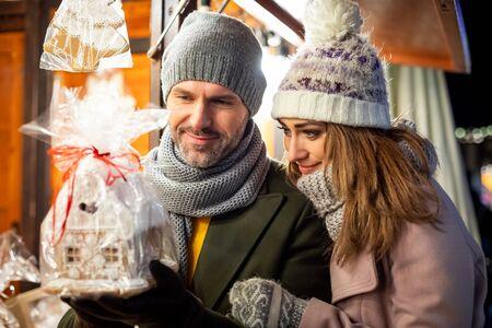 Una bonita pareja pasa tiempo juntos en el mercado navideño mirando productos en los puestos