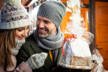 Loving couple visits the decorated Christmas market during the evening