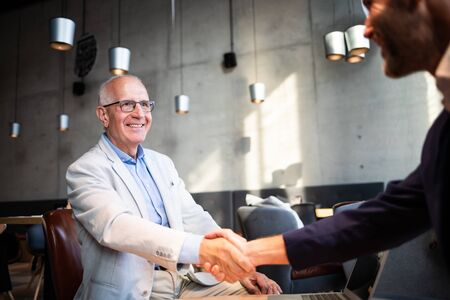 Senior businessman shaking hands during meeting in cafe Banco de Imagens
