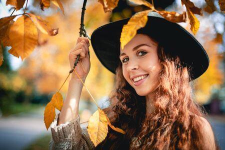 Jonge vrouw die in de herfst buiten loopt en geniet van het weer