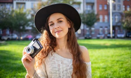 Lifestyle portrait of stylish girl with retro camera during walk in city street